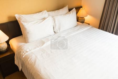 Photo pour Oreiller confortable blanche sur lit avec intérieur décoration lampe de chambre à coucher - image libre de droit
