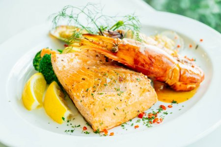 Mixed grilled seafood steak with salmon prawn and other meat in white plate