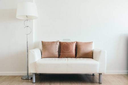 Photo for Comfortable pillow on white sofa with light lamp decoration in living room interior - Royalty Free Image