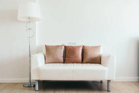 Foto de Almohadilla cómoda en el sofá blanco con decoración de lámpara de luz en el interior de la sala de estar - Imagen libre de derechos