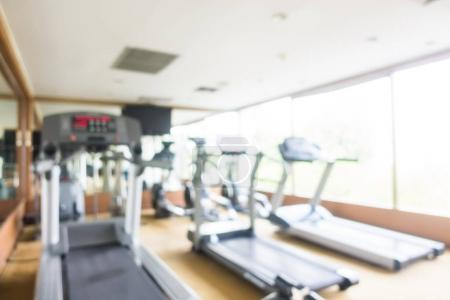 Abstract blur and defocused sport fitness equipment in gym interior for background