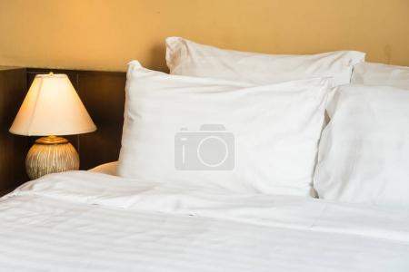 Photo pour Oreiller confortable blanc sur lit avec lampe de lumière décoration intérieure de la chambre - image libre de droit