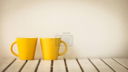 Yellow coffee cup on table with copy space