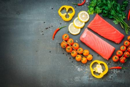 Photo for Raw tuna fish fillet meat on wooden cutting board with vegetable and ingredient for cooking on black stone background - Royalty Free Image