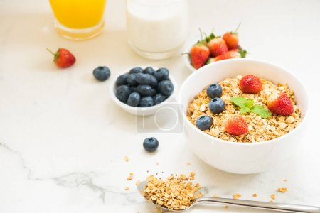 Photo for Healthy Breakfast set Granola with blueberry and strawberry and black coffee , Milk and Orange juice on white stone table background - Royalty Free Image