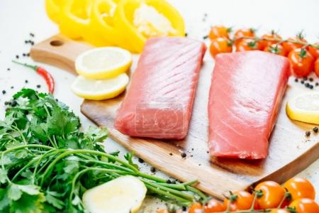 Raw tuna fish fillet meat on wooden cutting board with vegetable and ingredient for cooking