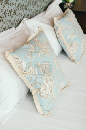Comfort pillow on bed with light lamp decoration in hotel bedroom interior