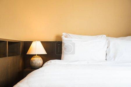 White comfortable pillow on bed with light lamp decoration interior of bedroom
