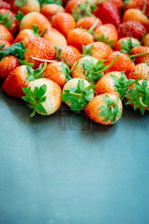 Strawberry fruit on black stone background with copy space