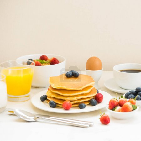 Photo for Healthy Breakfast set with Pancake and Granola with blueberry and strawberry and black coffee , Milk and Orange juice on white stone table background - Royalty Free Image