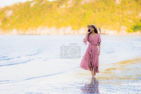 Photo pour Portrait jeune beau sourire asiatique de promenade de femme heureux et parlant le téléphone portable autour de l'océan de mer de plage pour le voyage de loisirs dans les vacances de vacances - image libre de droit