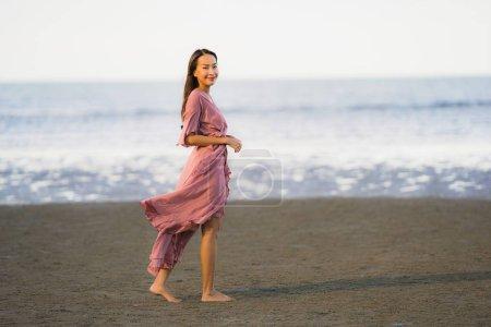 Photo pour Sourire de marche de femme asiatique de portrait et heureux sur la mer et l'océan de plage pour le voyage de loisirs dans les vacances de vacances - image libre de droit