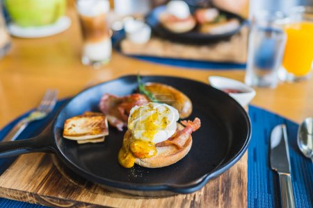 Photo for Breakfast set with egg benedict sausage in hot pan on wooden table - Royalty Free Image