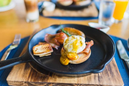 Photo pour Petit déjeuner avec saucisse aux oeufs dans une poêle chaude sur une table en bois - image libre de droit