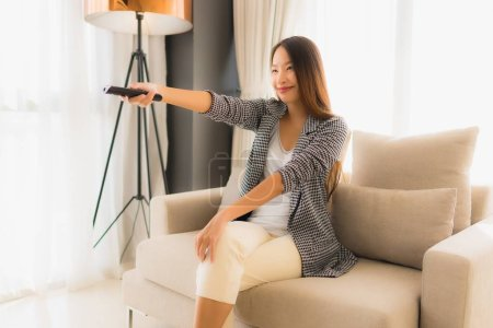 Photo for Portrait beautiful young asian women change channel tv in living room interior - Royalty Free Image
