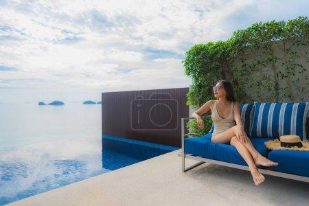 Photo pour Portrait jeune femme asiatique relax sourire heureux autour de la piscine à l'hôtel et station balnéaire pour vacances concept de voyage - image libre de droit