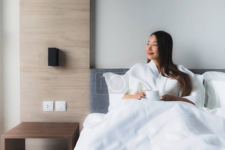 Portrait beautiful young asian women with coffee cup on bed