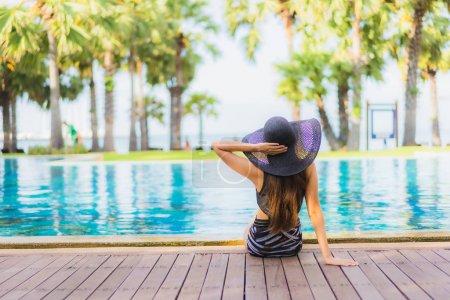 Photo pour Portrait belles jeunes femmes asiatiques heureux sourire se détendre autour de la piscine près de la mer plage océan dans la station hôtelière - image libre de droit