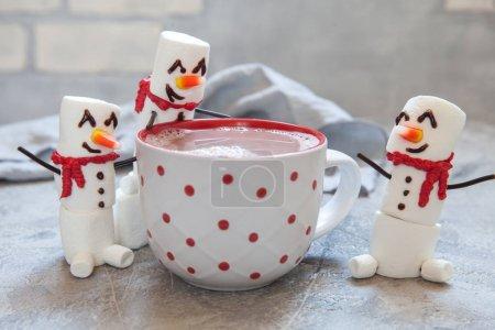 Photo pour Mug rouge avec du chocolat chaud avec bonhomme de neige fondue guimauve - image libre de droit