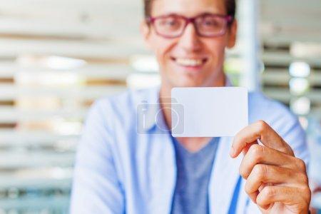 man holding blank name card.