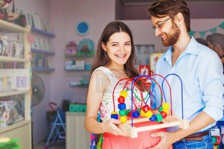 Photo pour Jeune couple de parents qui achètent un jouet pour bébé - image libre de droit