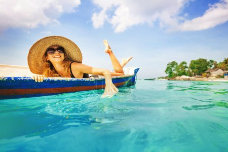 woman lying in boat on paradise island