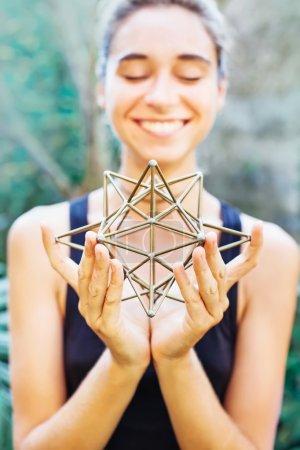 Photo pour Femme souriante et méditant sur la géométrie sacrée - image libre de droit