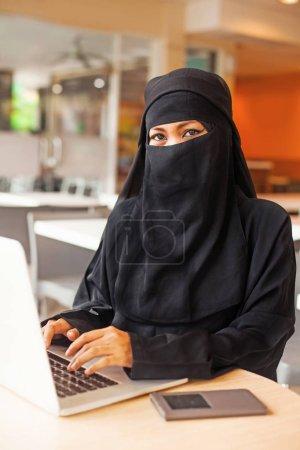 Photo pour Jeune femme arabe en utilisant un ordinateur portable - image libre de droit