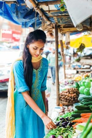 young  woman picking vegetables from an open market shop