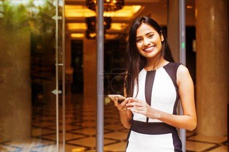 Photo pour Jeune femme indienne tenant le téléphone - image libre de droit