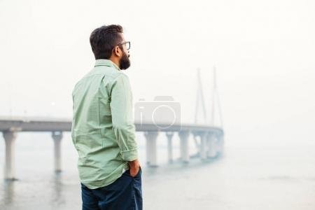 indian man standing and thinking in front of the bridge in mumbai