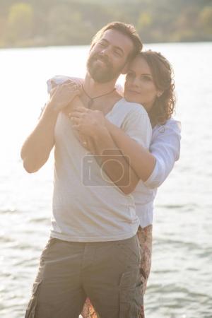 lovely couple hugging near lake
