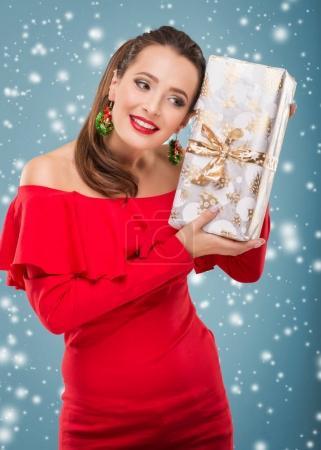 Beautiful santa Woman holding a gift box