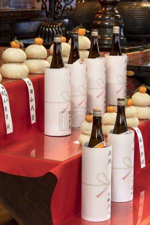 Photo pour Tokyo, Japon - 07 janvier 2019 : tokyo, Japon - 07 janvier 2019 : des bouteilles de liqueur de riz saké placées en offrandes devant une boule de riz kagami mochi surmontée d'une clémentine pour les célébrations du Nouvel An au temple Gokokuin de Tokyo . - image libre de droit