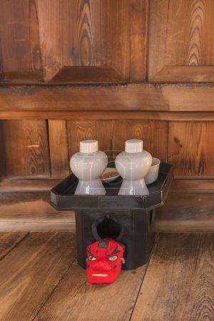 Photo pour Petit masque rouge du dieu Tengu des montagnes devant un plateau noir sanpou en bois de cyprès surmonté d'offrandes shintoïstes composées de saké omiki dans deux bouteilles de heishi, riz dans une assiette de hirazara et eau dans un bol de mizutama . - image libre de droit