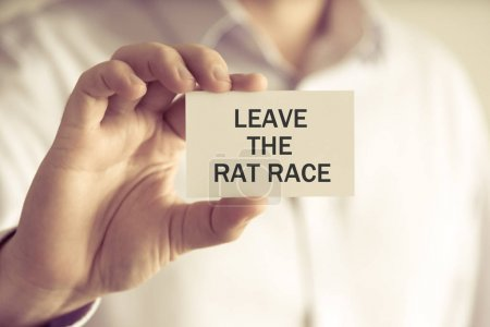 Businessman holding LEAVE THE RAT RACE message card