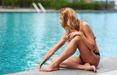Beautiful young blonde by the pool