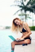 Beautiful young woman with laptop by the pool