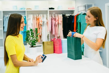Photo for Young woman in shop with credit card in hand receiving her purchase from female seller - Royalty Free Image