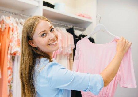 Photo pour Shopping concept de vente jeune femme choisir robe pendant les achats au magasin de vêtements dans le centre commercial - image libre de droit
