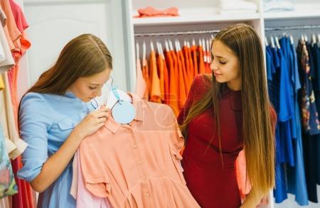 Women shopping and choosing dresses