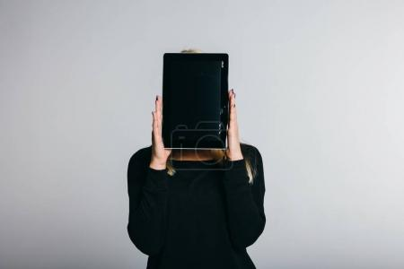 woman covering face with tablet computer