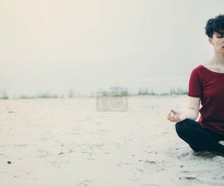 Photo pour Jeune femme méditant sur la plage en position lotus - image libre de droit