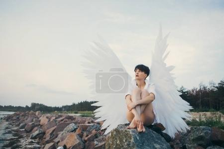 woman with white wings sitting near the river