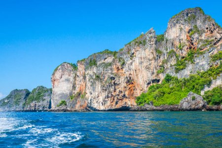 Cliff and the clear sea with a boat near Phi Phi island in south