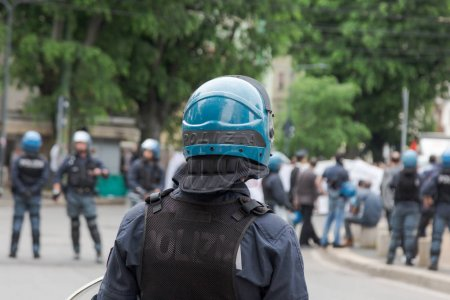 Photo for MILAN, iTALY - MAY 5, 2018: Riot police in full tactical gear stand ready to confront anarchic activists during a demonstration in the city streets. - Royalty Free Image