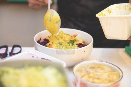 Photo pour Main d'un cuisinier préparant un plat coloré et sain - image libre de droit