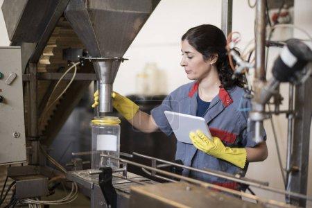 Photo pour Une travailleuse avec des comprimés révise une courroie transporteuse dans une usine alimentaire - image libre de droit