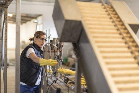 Photo pour Une travailleuse révise une machine en usine avec des lunettes et des gants de protection - image libre de droit
