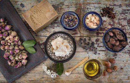 Photo pour Mélange d'herbes, fleurs, noix d'argan et huile, noix de karité et beurre, anis et savon d'Alep sur table en bois - image libre de droit